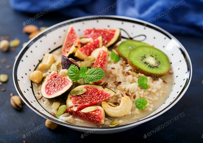 Delicious and healthy oatmeal with figs, nuts, kiwi and seeds.