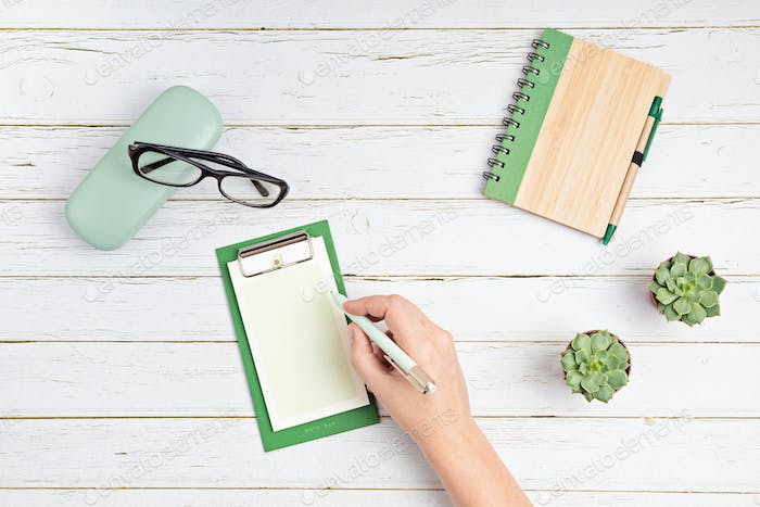 Hand with pen writing in blank notepad and glasses on white wooden background