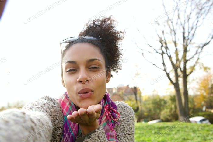 Selfie Porträt einer jungen Frau bläst ein Kuss