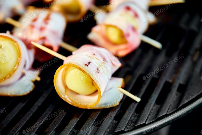 Grilled potato with bacon on gas grill .