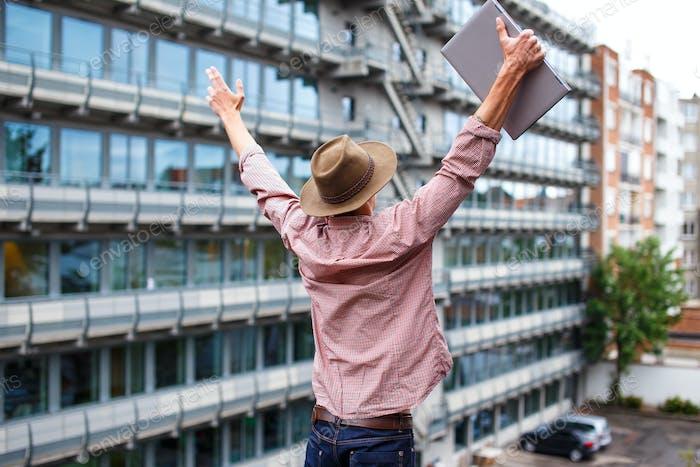 Ein Mann, der Laptop auf dem Dach benutzt.