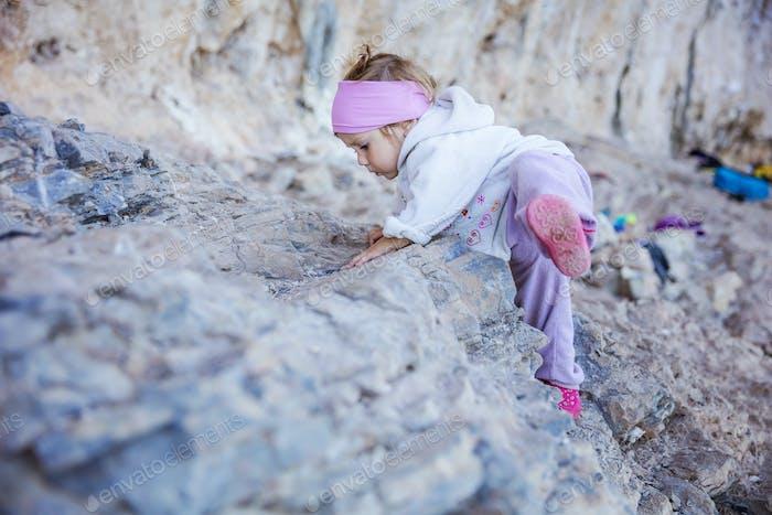 Little girl playing on rocks near climbing sector