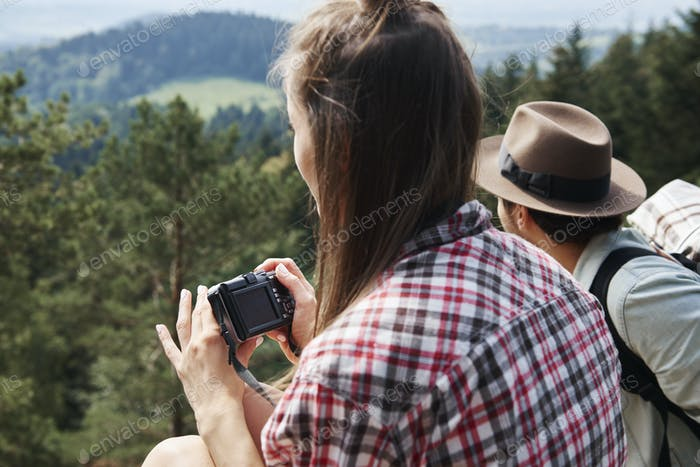 Side view of backpacker using camera in the mountains