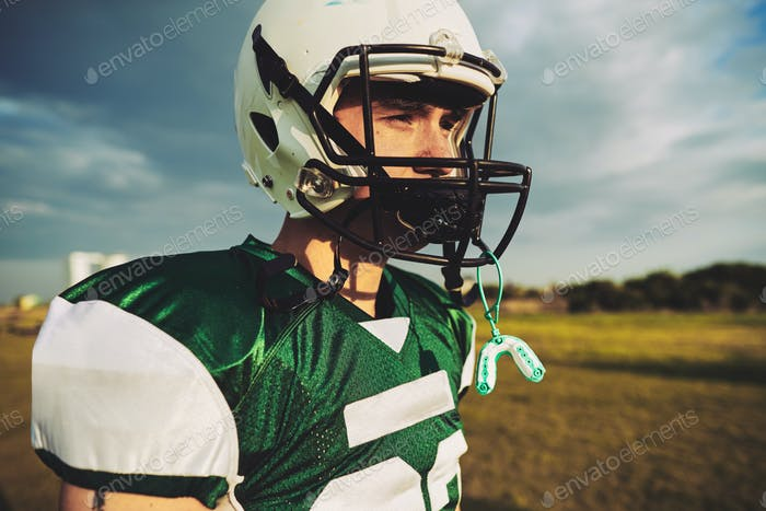 Young American football player taking a break during practice