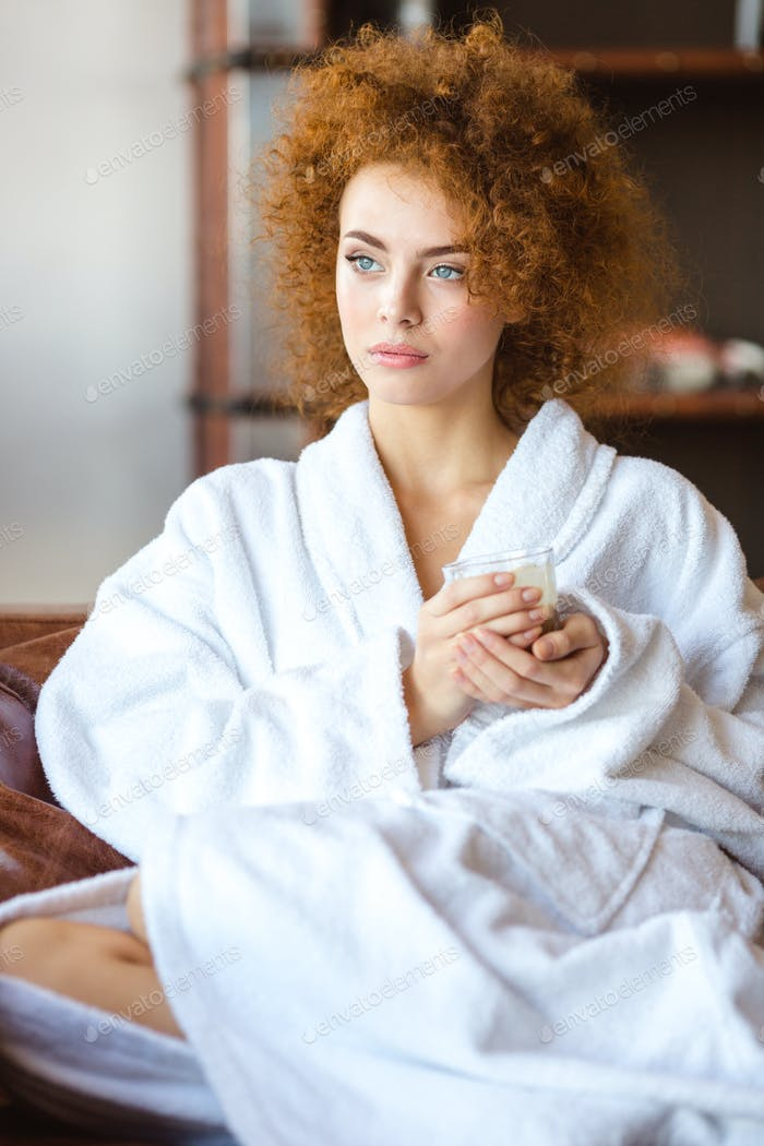 Beautiful pensive woman in white bathrobe sitting and relaxing