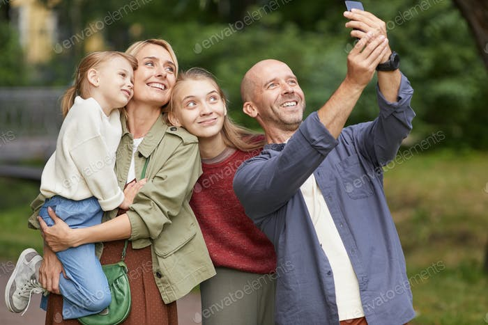 Happy Family Talking Selfie in Park