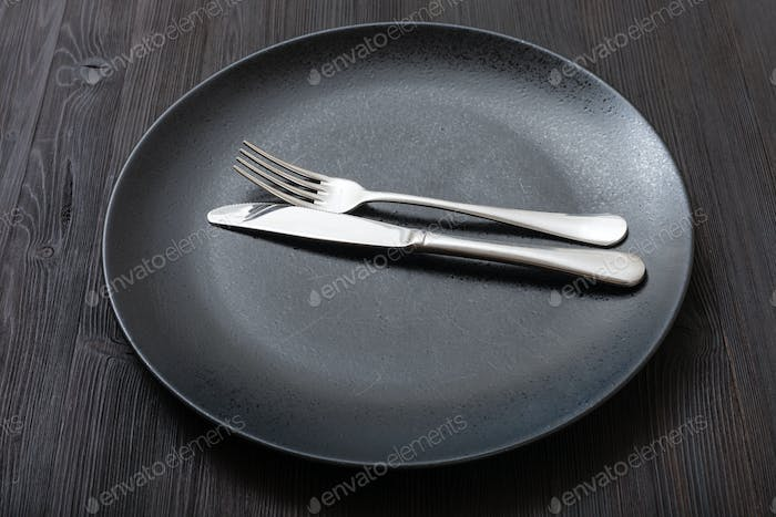 black plate with parallel knife, spoon on dark