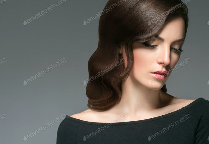 Beautiful woman with curly hairstyle portrait over gray background. Female young beauty.