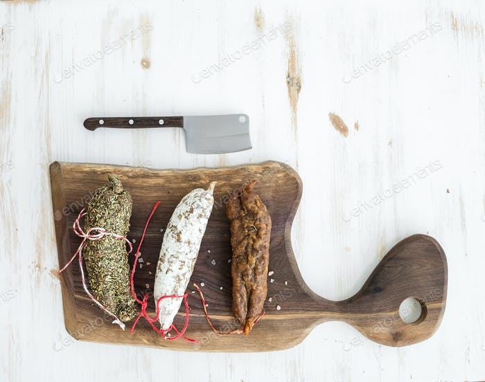 French alsacian smoked salamis on rustic walnut wooden chopping board over white backdrop, top view