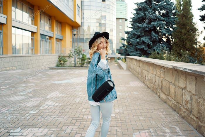 Кавказская женщина гуляет по городу, слушая музыку