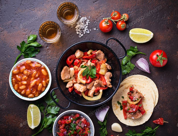 Concept of Mexican food.  Salsa, tortilla, beans, fajitas and tequila