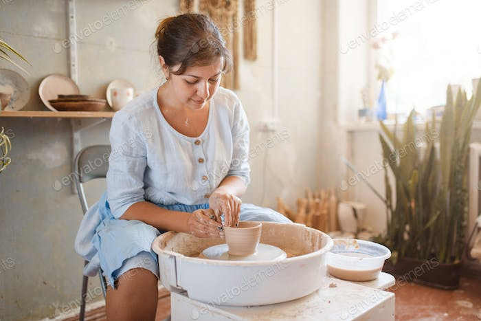 Female master making a pot on pottery wheel