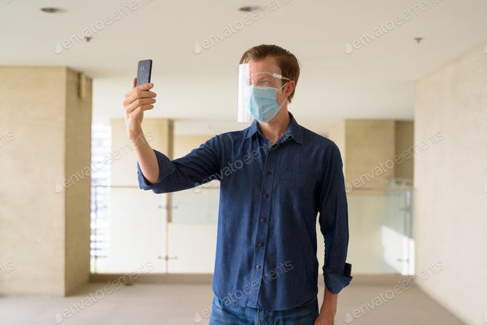 Young man with mask and face shield taking selfie at modern building