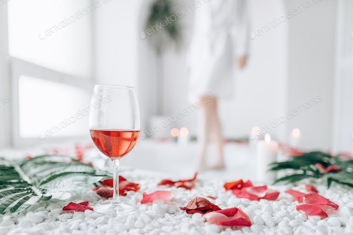 Woman dips legs into the bath, rose petal decor