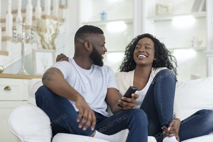 Cheerful couple sitting on couch watching funny videos on tv