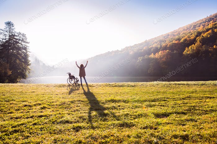 Senior woman standing by the wheelchair in autumn nature.