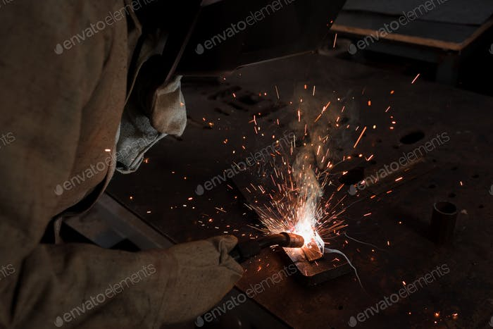 Cropped Image of Worker in Protection Mask Welding Metal at Factory
