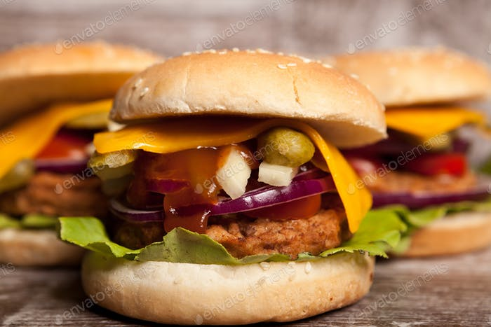 Delicious home made snack burgers on wooden plate