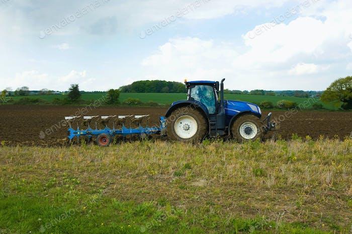 Ein Traktor erschütternd, Pflügen im Stoppeln in einem Feld.