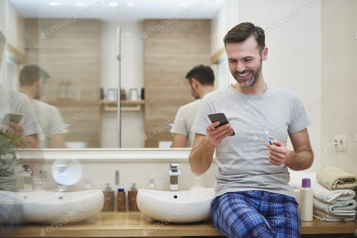 Man brushing teeth and using mobile phone in the bathroom