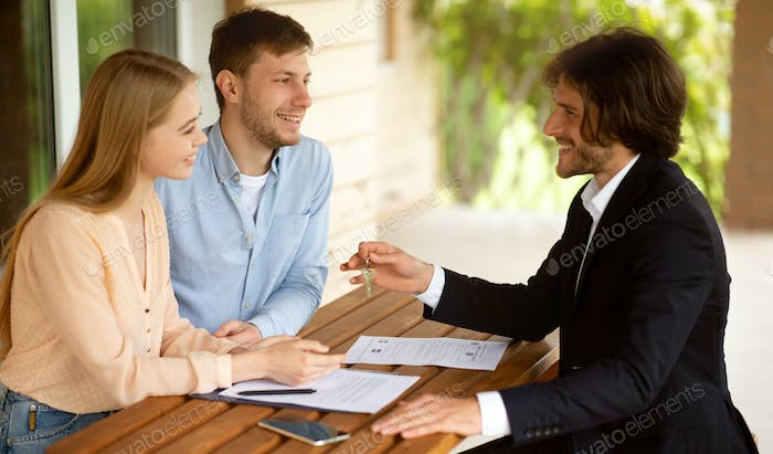 Real estate broker giving house key to millennial couple after signing property agreement at table