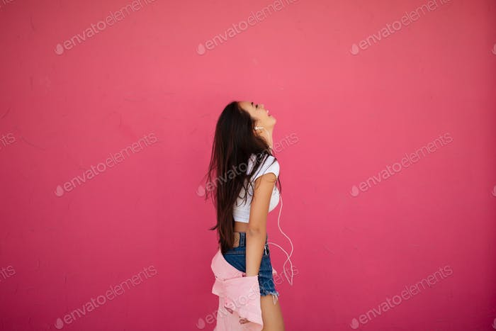 Beautiful happy girl with dark long hair listening music in earphones on pink background