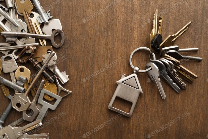 Bunch of keys with house trinklet on wooden table