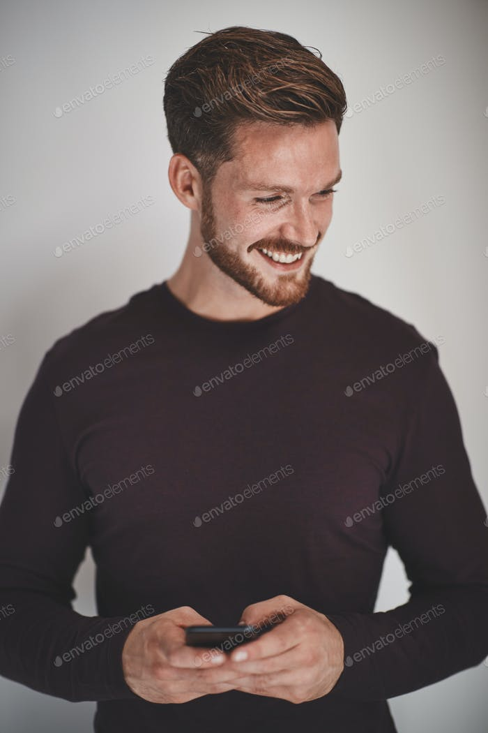 Laughing young entrepreneur reading text messages against a gray background