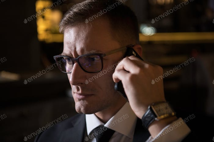 portrait of serious handsome elegant caucasian businessman talking on the phone