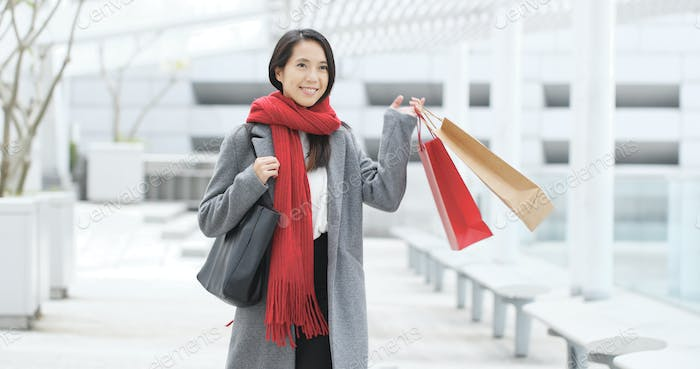 Excited woman holding shopping bag