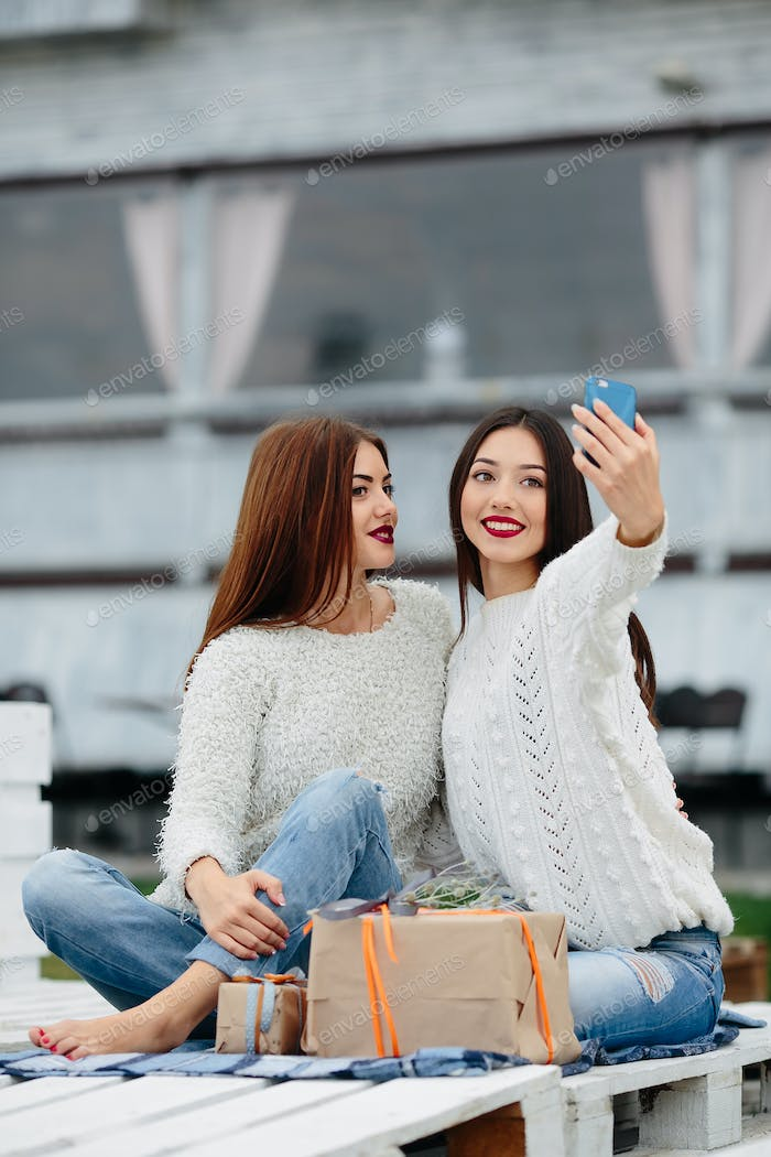 Two girls make selfie with gifts