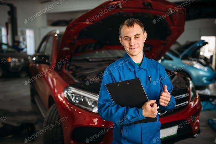 Techniker mit Notebook, Auto mit geöffneter Haube