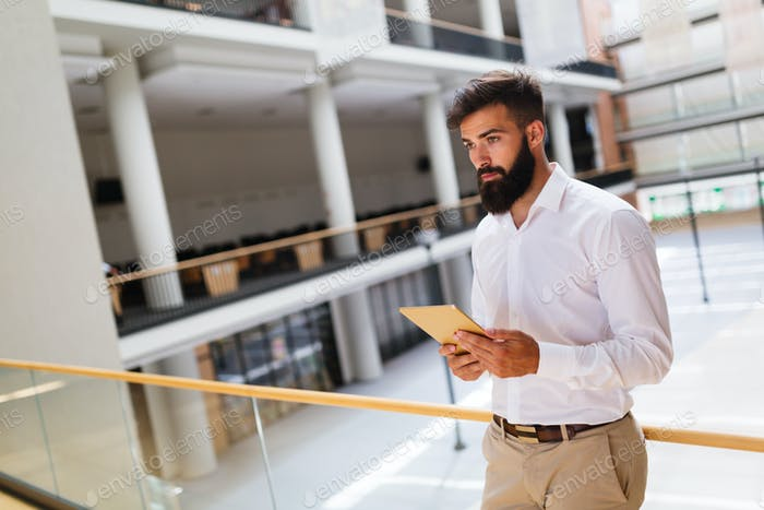 Handsome young businessman using his digital tablet