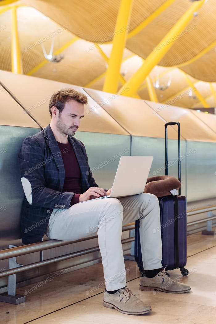 Young attractive man sitting at the airport working with a lapto