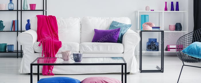 Pink blanket on white couch in flat interior with table and blue