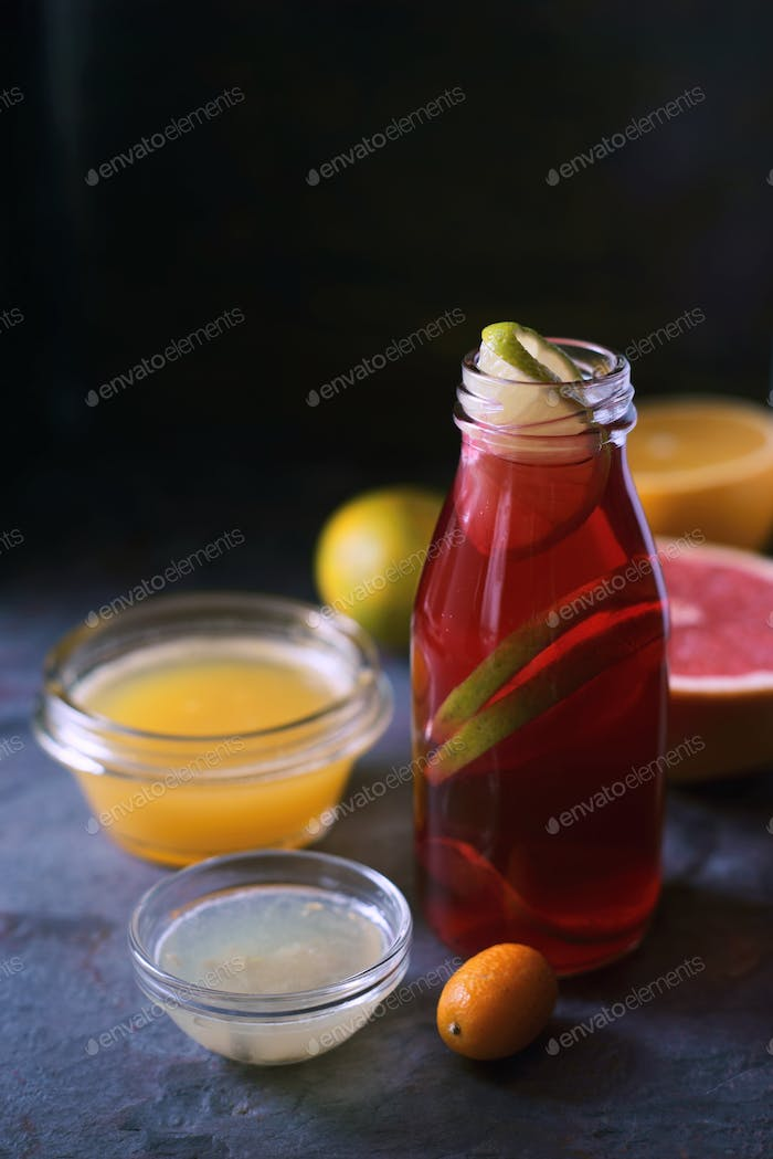 Glass bottle with citrus cocktail on the dark  stone background