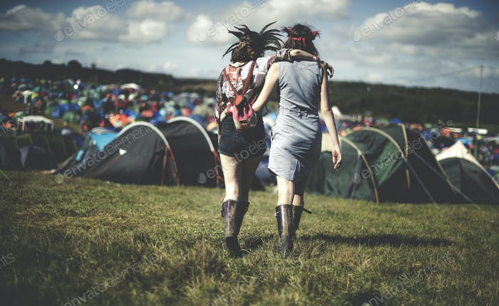 Rear view of two young women at a summer music festival wearing feather headdresses, walking arm in