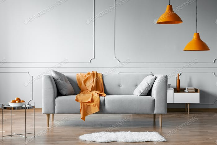 Orange blanket on grey scandinavian sofa, copy space on grey living room wall