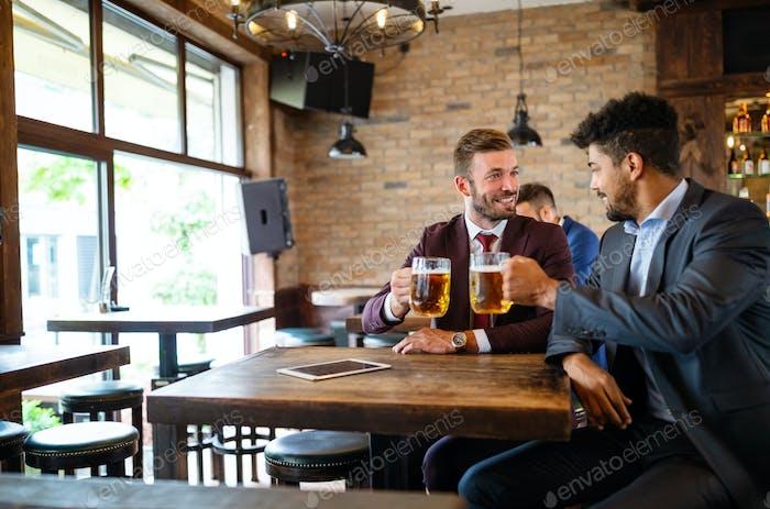 Ich habe ein Pint mit einem Freund. Fröhliche junge Männer Toasten mit Bier, während sie zusammen an der Bar sitzen
