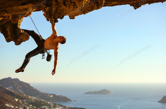 Young man climbing on roof of cave against view of coast