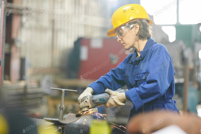 Woman Cutting Metal in Garage
