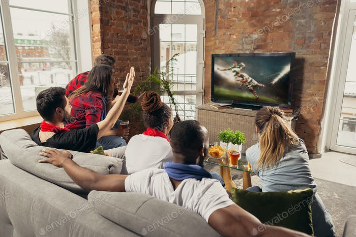 Excited group of people watching sport match at home