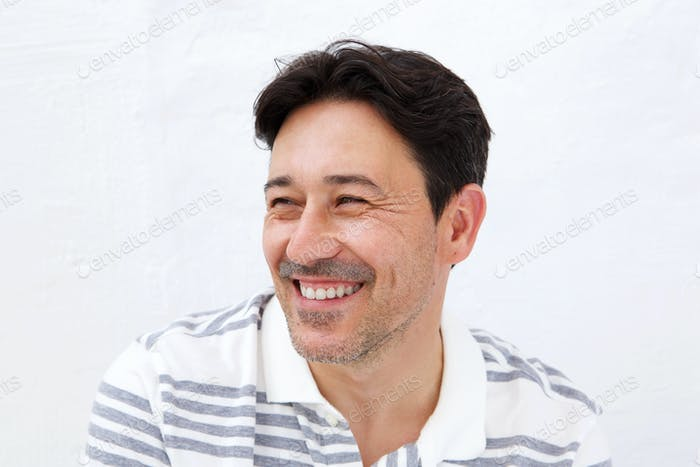 Older man looking away and smiling on white background