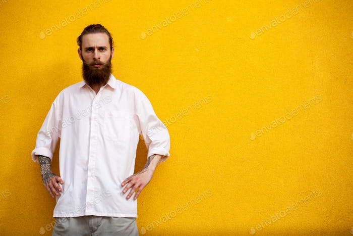 Portrait of tattooed bearded hipster on yellow wall
