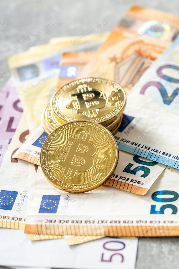 Bitcoins and euro banknotes. Coins of bitcoin.
