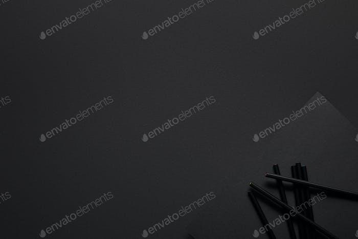 Lápices negros y papel sobre fondo negro
