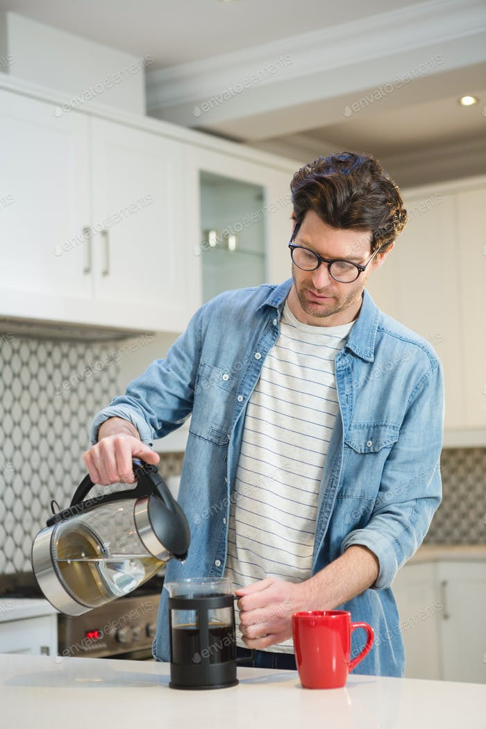 Man pouring coffee from mug into french press at home