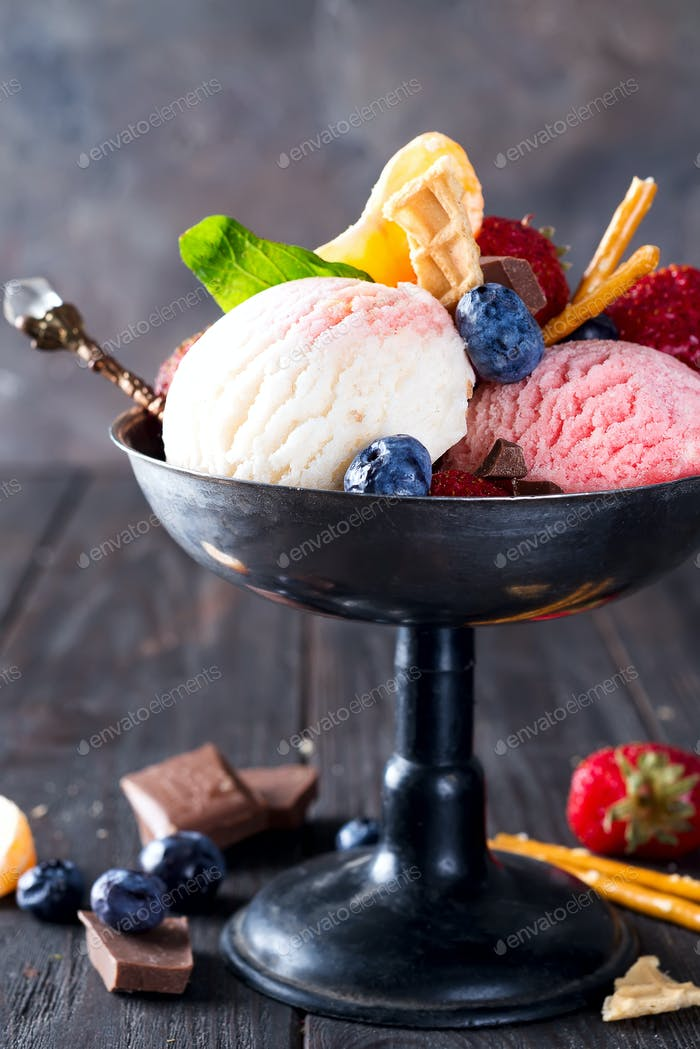 Trio of tasty lemon, vanilla and strawberry flavored frozen dessert ice cream in a metal bowl with
