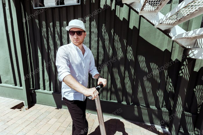 Modern man dressed white shirt and black pants standing at the street with electric scooter