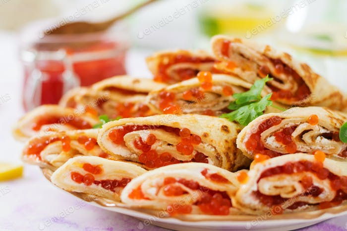 Pancakes with red caviar on plate. Russian cuisine. Maslenitsa